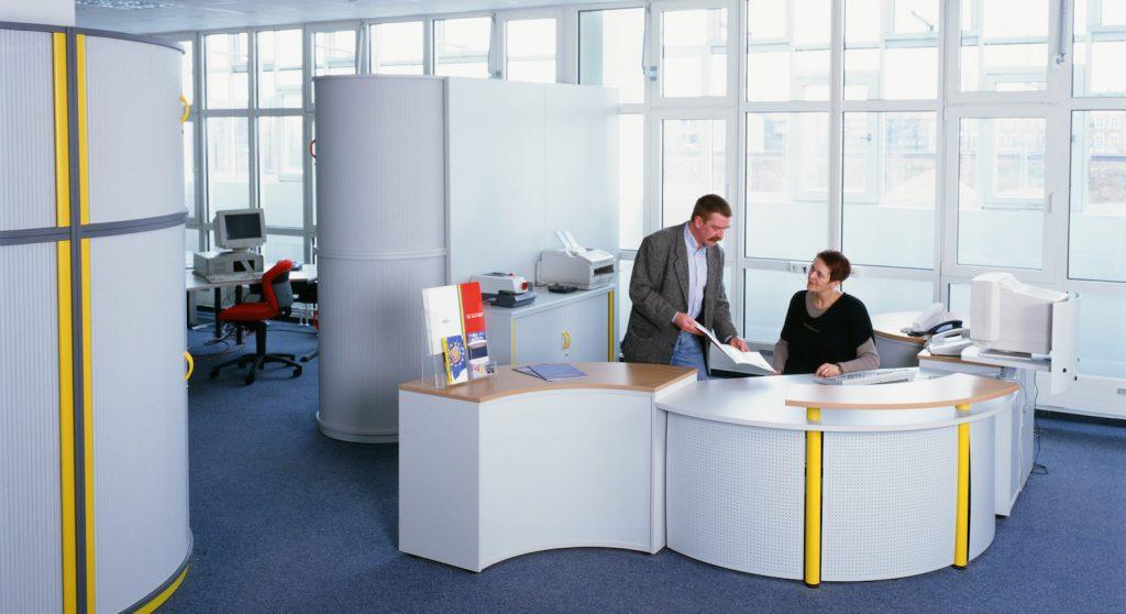 Mitte der 90er Jahre: Petra und Stefan Wirth stehen in einer offenen Bürolandschaft